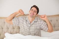 Man waking up in bed and stretching his arms Stock Photos