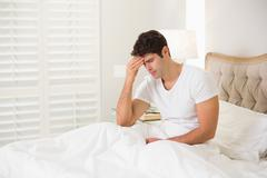 Young man suffering from headache in bed - stock photo
