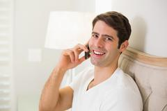 Casual smiling man using cellphone in bed - stock photo