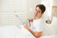 Smiling man having coffee while reading newspaper Stock Photos