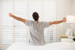 Rear view of a man stretching his arms in bed - stock photo