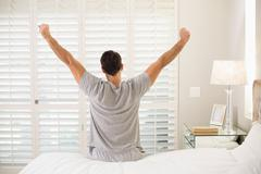 Rear view of man stretching his arms in bed - stock photo