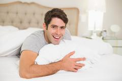 Close up portrait of a cheerful man resting in bed - stock photo