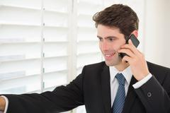 Smiling businessman peeking through blinds while on call - stock photo