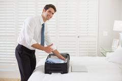 Smiling businessman unpacking luggage at a hotel bedroom - stock photo