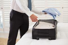 Mid section of businessman unpacking luggage at hotel - stock photo