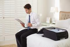 Businessman with coffee cup and newspaper by luggage at hotel room - stock photo