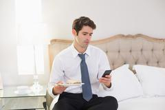 Well dressed man text messaging in bed at home Stock Photos