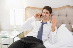 Smiling well dressed man using mobile phone in bed Stock Photos
