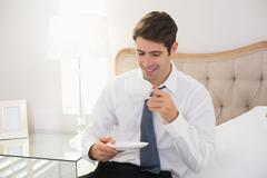 Smiling well dressed man drinking tea in bed - stock photo