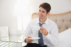 Smiling well dressed man with a cup of tea in bed Stock Photos