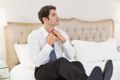 Elegant young businessman adjusting tie in bed - stock photo