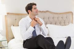 Smiling businessman adjusting tie in bed Stock Photos