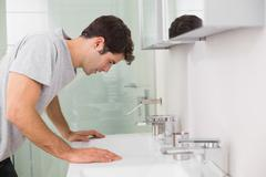 Tensed young man at washbasin in bathroom - stock photo