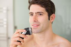 Smiling handsome shirtless man shaving with electric razor Stock Photos