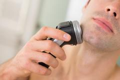 Extreme Close up of man shaving with electric razor Stock Photos