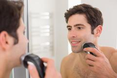 Reflection of shirtless man shaving with electric razor Stock Photos