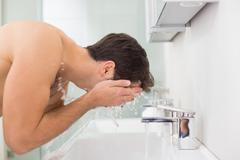 Shirtless young man washing face in bathroom - stock photo