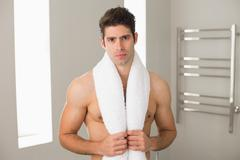 Shirtless man with towel around neck at home Stock Photos