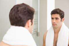 Tensed young man looking at self in bathroom mirror - stock photo
