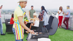 Happy group of young friends enjoying a rooftop barbecue in the city - stock footage