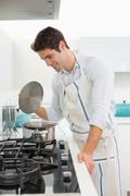 Smiling young man preparing food in kitchen - stock photo