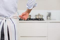 Mid section of a man wearing apron in kitchen - stock photo