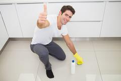 Man cleaning the kitchen floor while gesturing thumbs up - stock photo