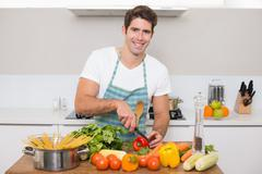 Stock Photo of Smiling young man chopping vegetables in kitchen