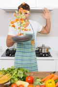 Cheerful man tossing vegetables in kitchen Stock Photos