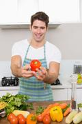 Smiling man holding out bell pepper with vegetables in kitchen - stock photo