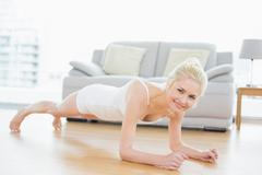Sporty woman doing push ups in fitness studio - stock photo