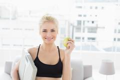 Smiling fit woman holding scale and apple in fitness studio Stock Photos