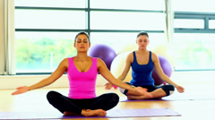 Lovely calm women meditating sitting in lotus position Stock Footage