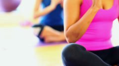 Mid section on meditating young women sitting on exercise mats - stock footage