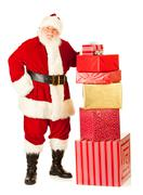 Stock Photo of santa: standing by large stack of gifts