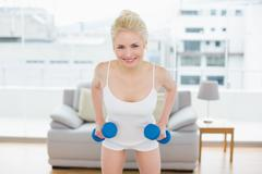 Stock Photo of Smiling woman with dumbbells at fitness studio