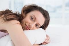Close up portrait of a pretty woman resting in bed - stock photo