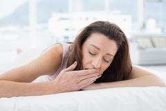 Nainen ammottava silmät kiinni sängyssä Kuvituskuvat