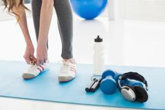 Woman tying shoes with sporty equipment on floor Stock Photos