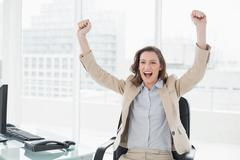 Elegant businesswoman cheering with hands raised in office Stock Photos