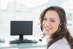 Businesswoman wearing headset in front of computer in office - stock photo