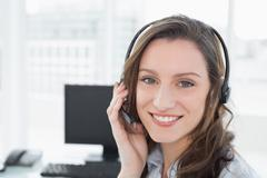 Portrait of businesswoman wearing headset in front of computer - stock photo