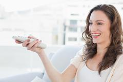Stock Photo of Smiling young woman with remote control sitting on sofa