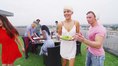Happy group of young friends enjoying a rooftop barbecue in the city Stock Footage