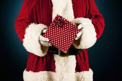 santa: holding a wrapped present - stock photo