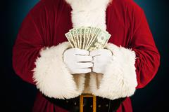 santa: santa holding fanned out cash - stock photo