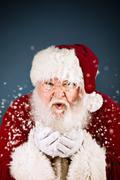 santa: santa claus blowing snow - stock photo