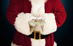 Santa: santa holding fanned out cash Stock Photos