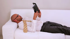 Tired businessman falling asleep on couch - stock footage
